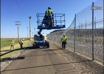 Fence OKC installing 12' + 1' Chain Link Federal Prison Fence with 3 rows of razor wire.